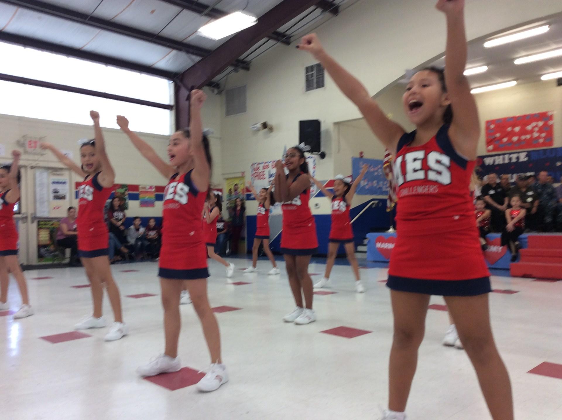 Cheerleaders performing stunts in the gym.