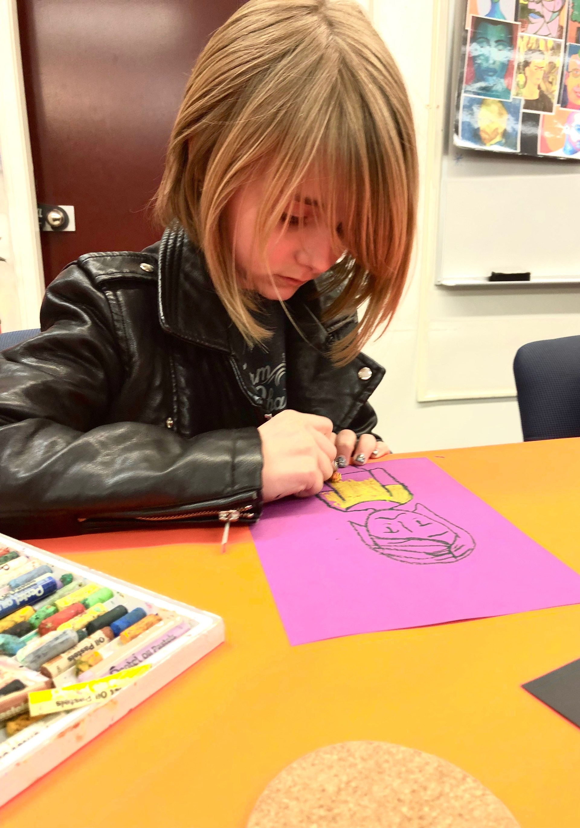 A girl using oil pastels to create a self-portrait.