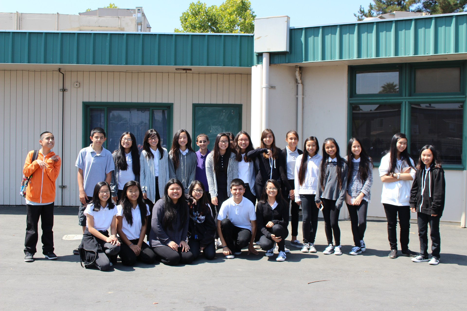 large group of students standing in front of school wall