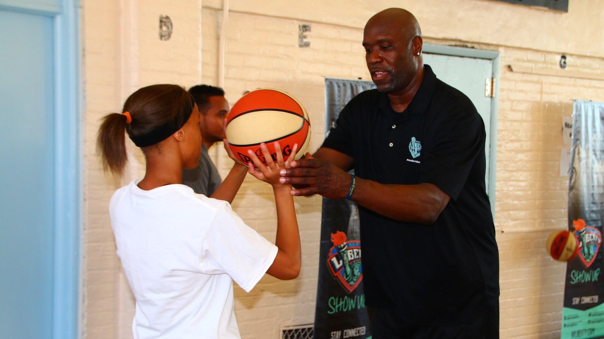 Coach teaching a girl how to shoot a basketball