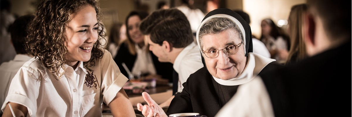 A photo of students sitting at a cafeteria table with a nun