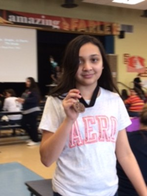 Student at the academic meet showing her medal.