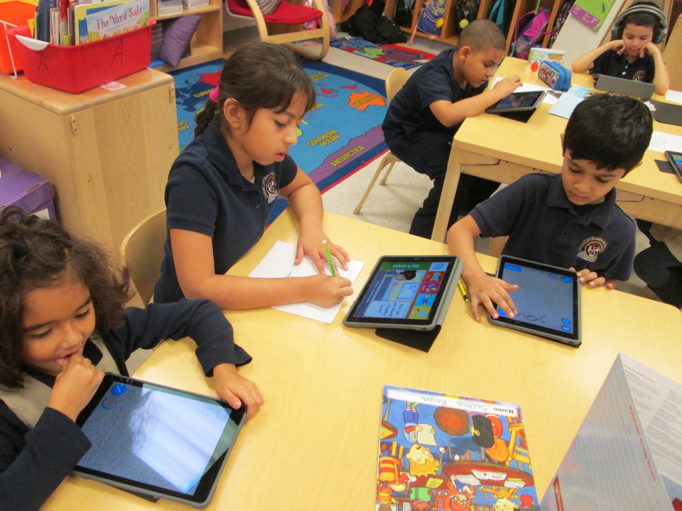 group working with their ipads to solve problems