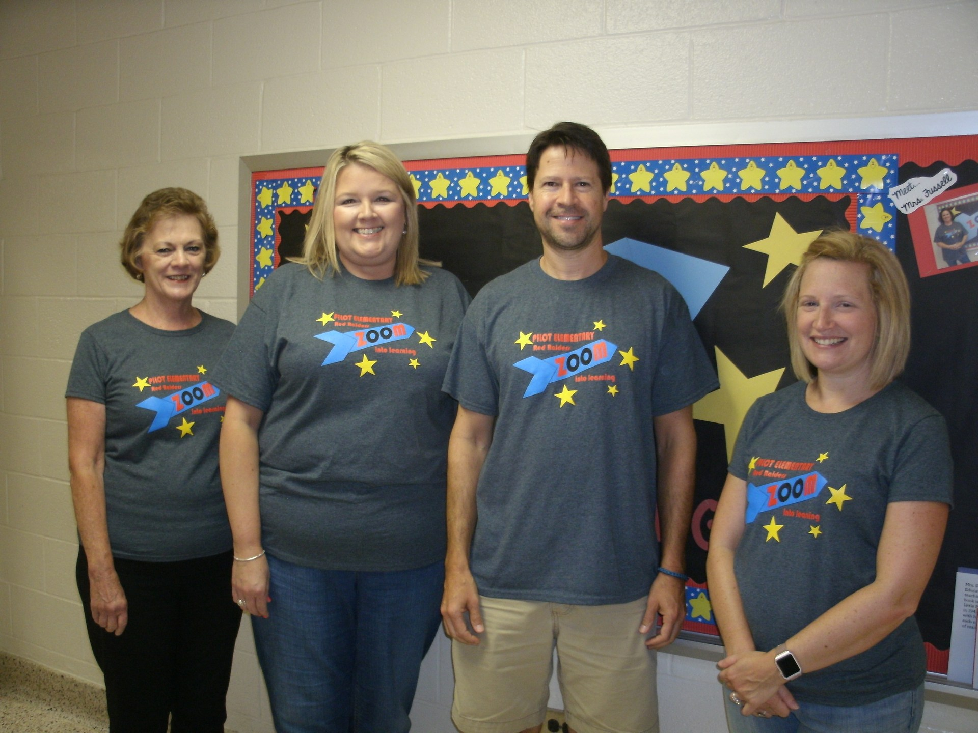 Four third grade teachers are standing in front of a bulletin board.