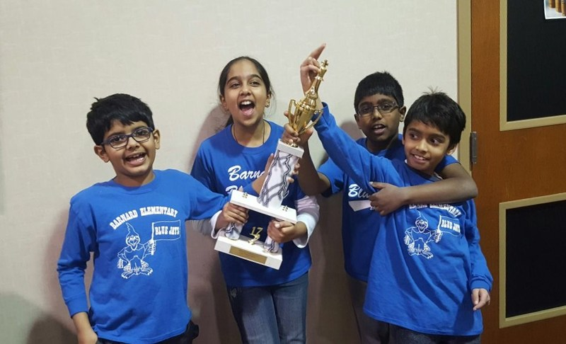 4 students holding a trophy