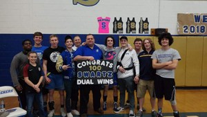 Picture of Coach Swartz and the wrestling team holding the 100th win sign.