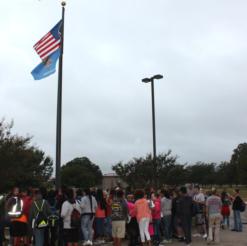 Students gathered around the flag pole at AMS