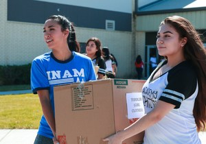Knightettes Director and Student carry box of donations to truck