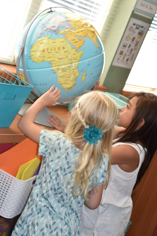 kindergarten students at orientation exploring a globe