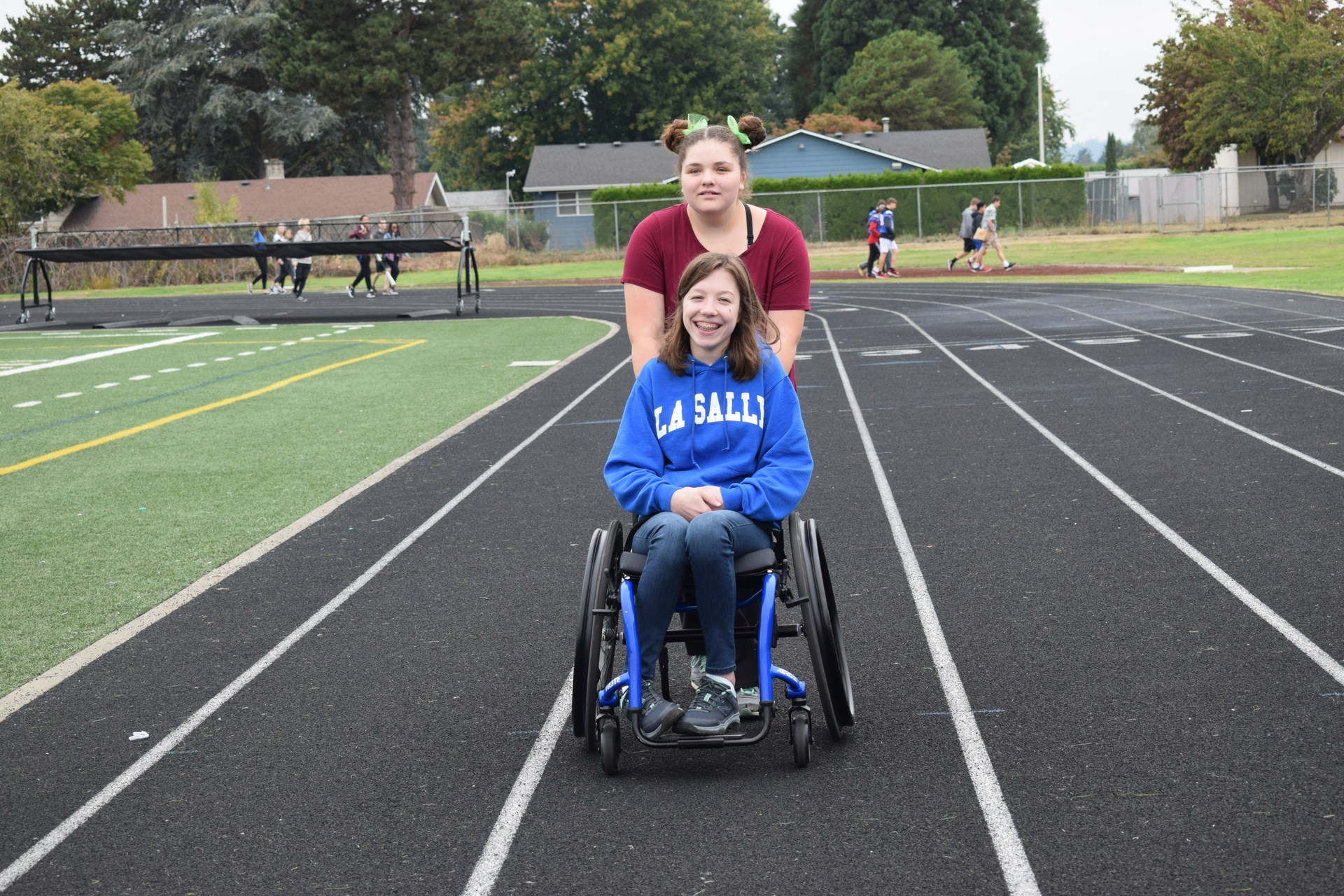 Girl pushing another girl in wheelchair