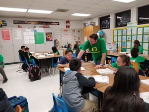 BPUSD_KENMORE_2: Kenmore Elementary School Bernardo Perdices, clad in University of Oregon green, works with students on a math performance task.