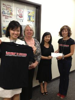 .  May Lin Tan hands a much-needed check for $600 to Dr. Laurel Bear to support the continued work of Gateway to Success in Alhambra District schools. The posters in the window behind them are winners of the district anti-bullying poster campaign.