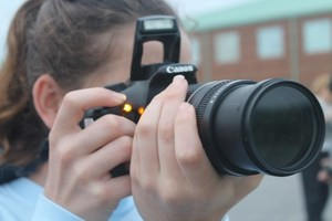 Picture of a student using a camera to take a picture.