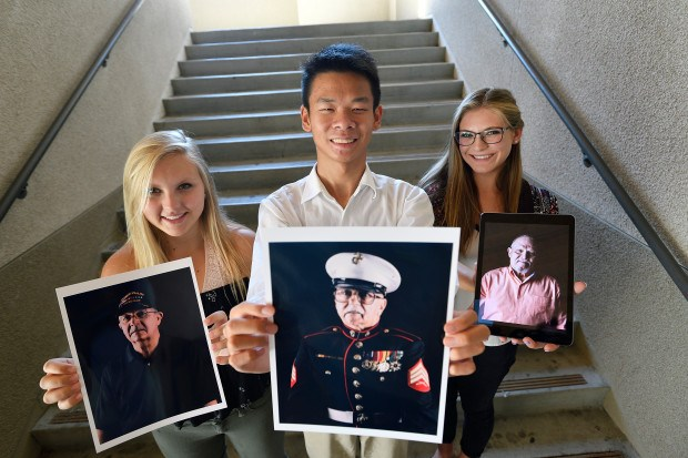 YLHS students holding photos of Vietnam veterans