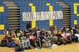 Students in rocking chairs with sign in the background,