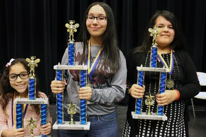 Picture of the top three spellers with their trophies.