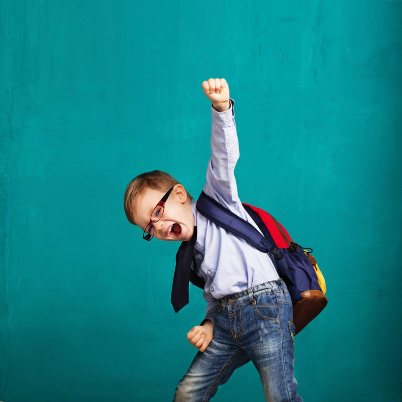 Little boy with backpack pumping fist into air with excitement