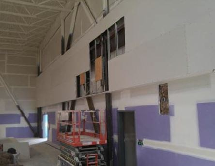 Gym walls with partial drywall and steel framing with construction crew at work