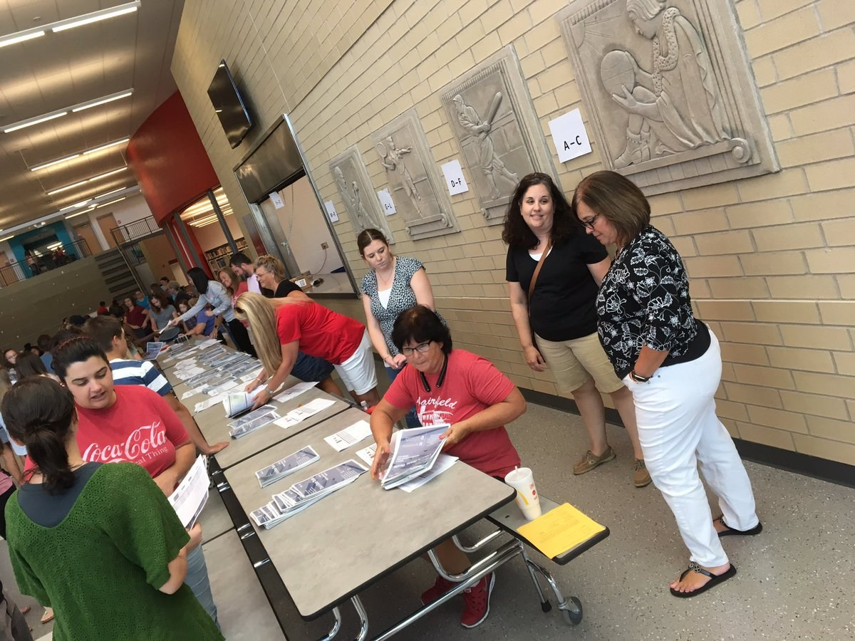 Former and current staff members assist students during schedule pickup.