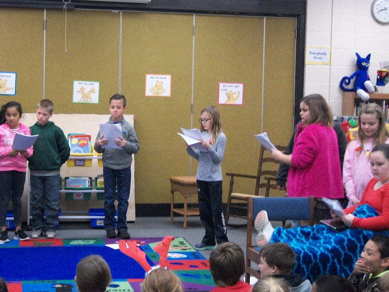Students act out a play in front of classmates.
