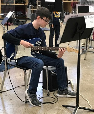 picture of Trenton practicing guitar in the RCJH band hall.