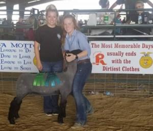 Student, teacher and lamb posing at livestock show