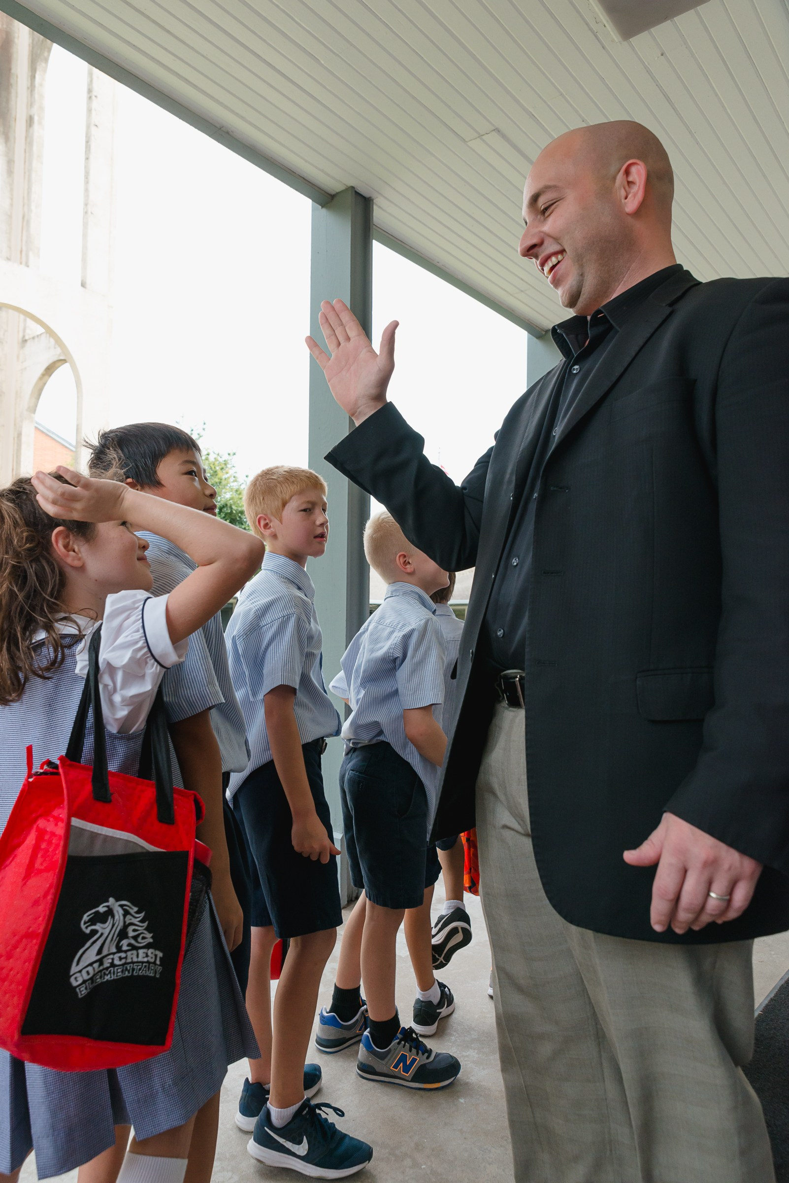 Head of School high-fives students