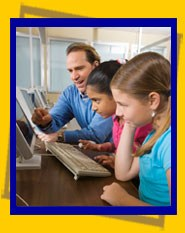 Teacher and students looking at computers