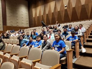 students in blue t-shirts sitting in an auditorium