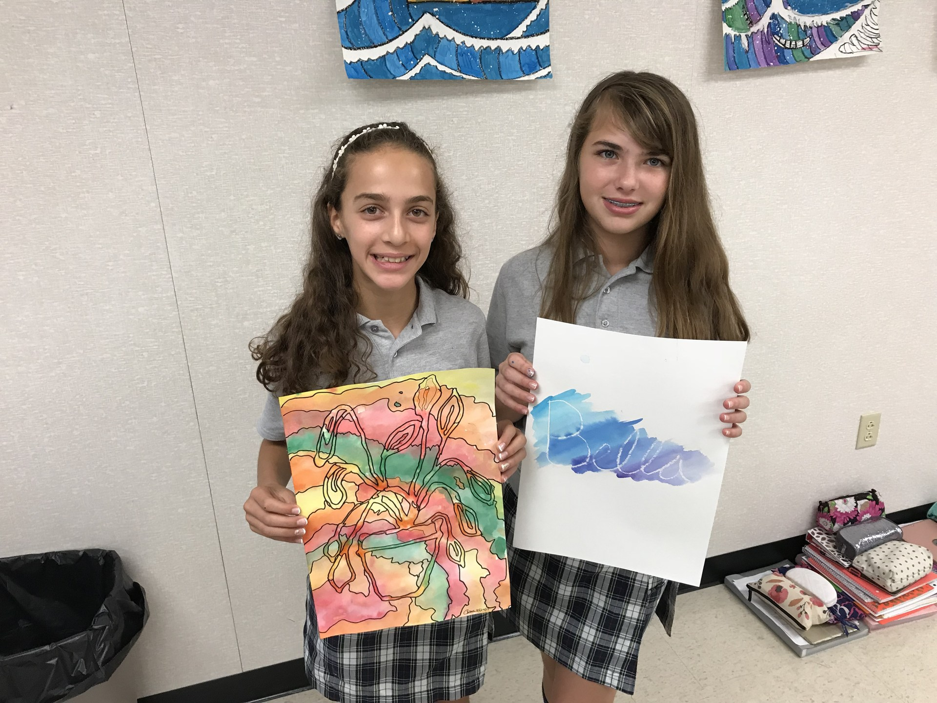 Two girls pose with drawings