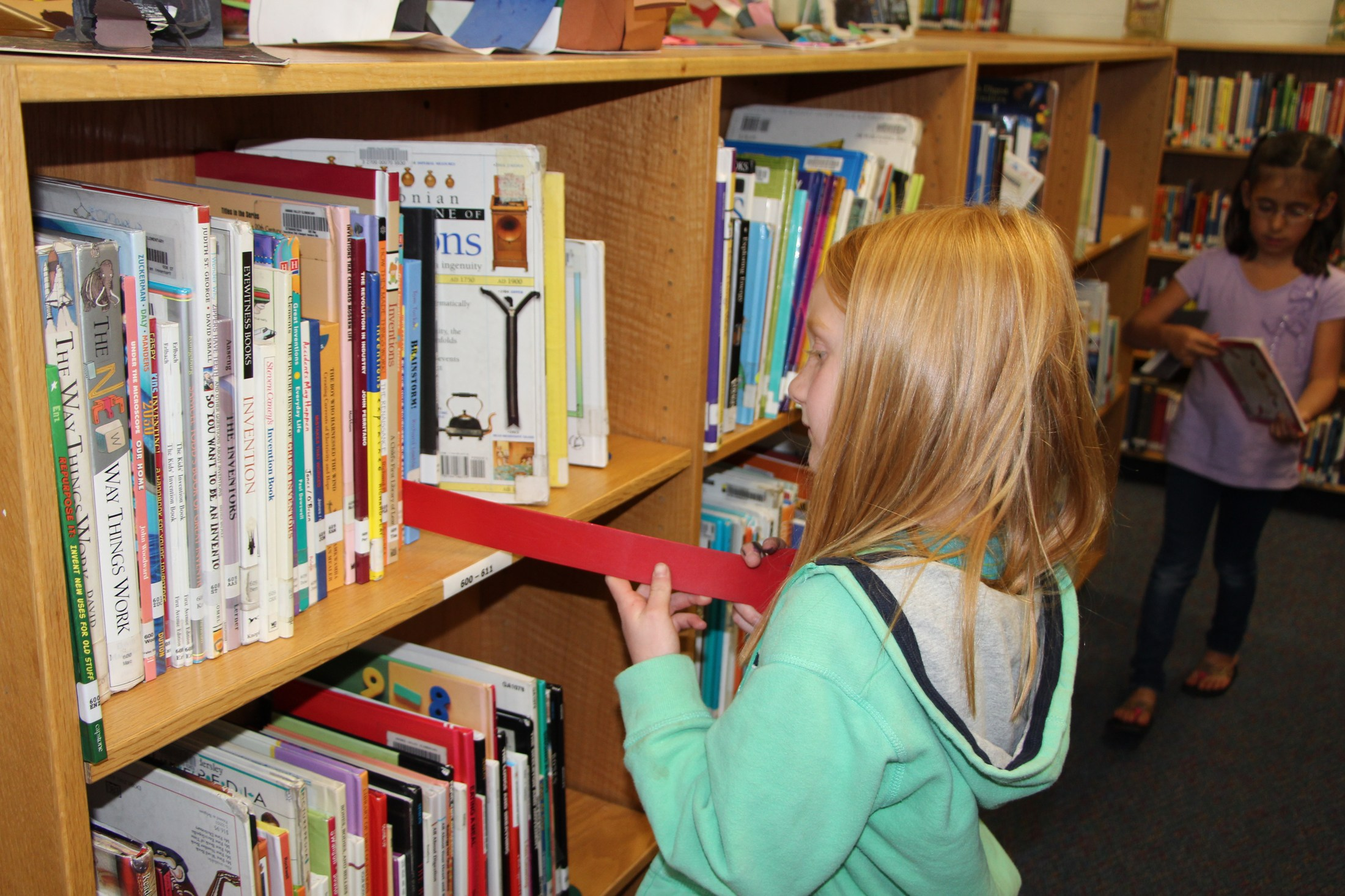 Child using shelf marker in library.