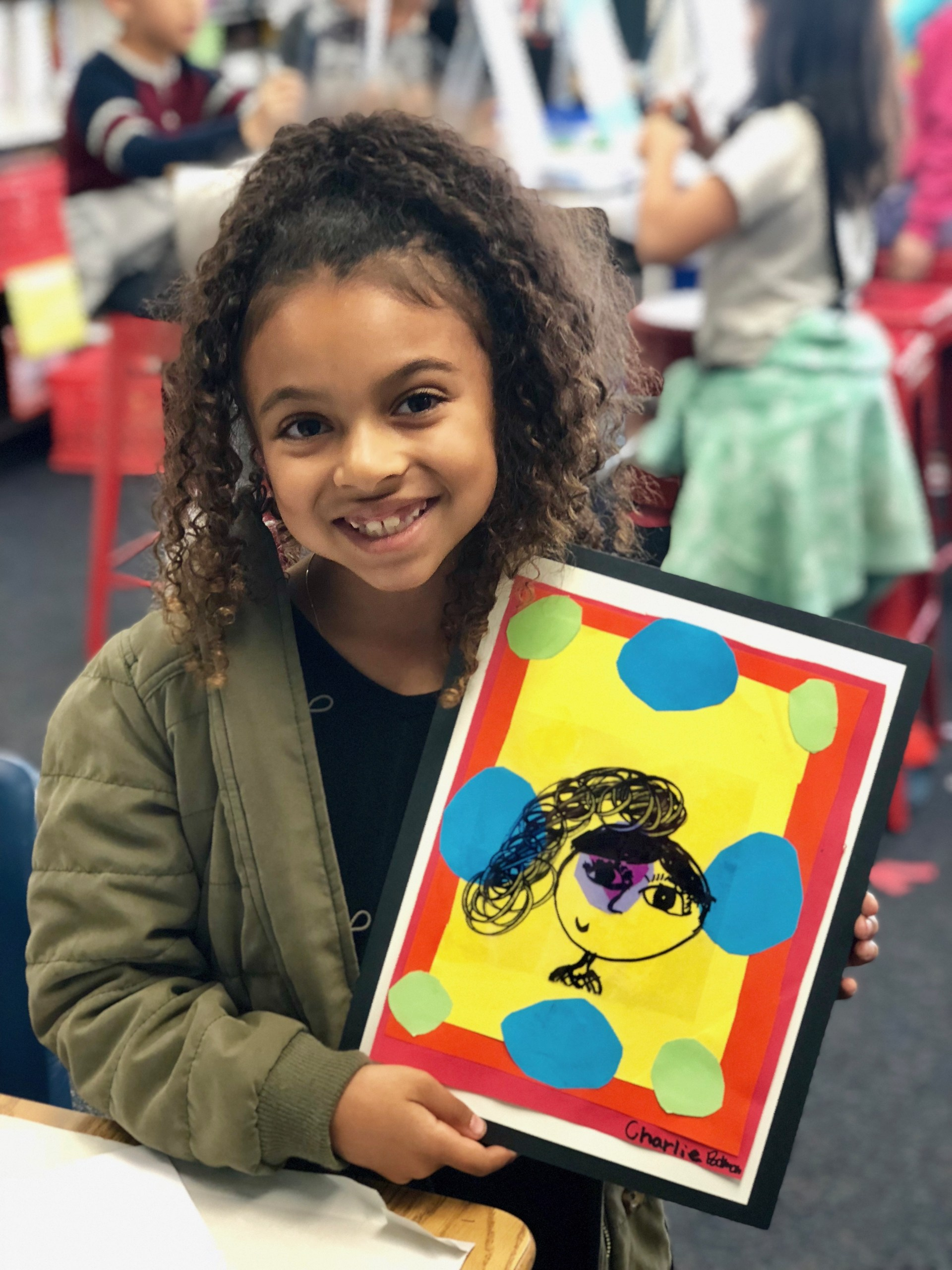 A girl showing her self-portrait on a colorful background.