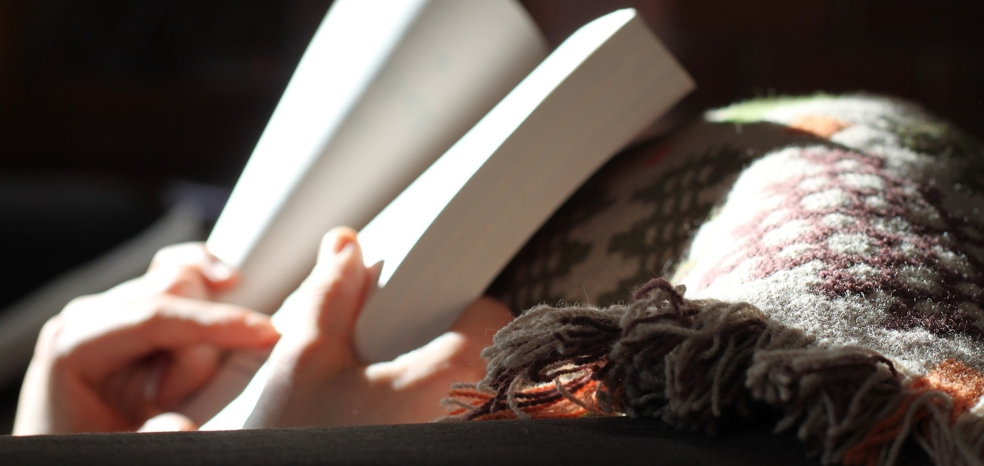 Image of hands holding an open book