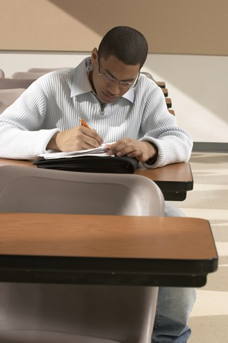 Student sitting on desk writing on a piece of paper