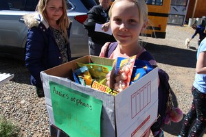 Image of student carrying a box of donations.