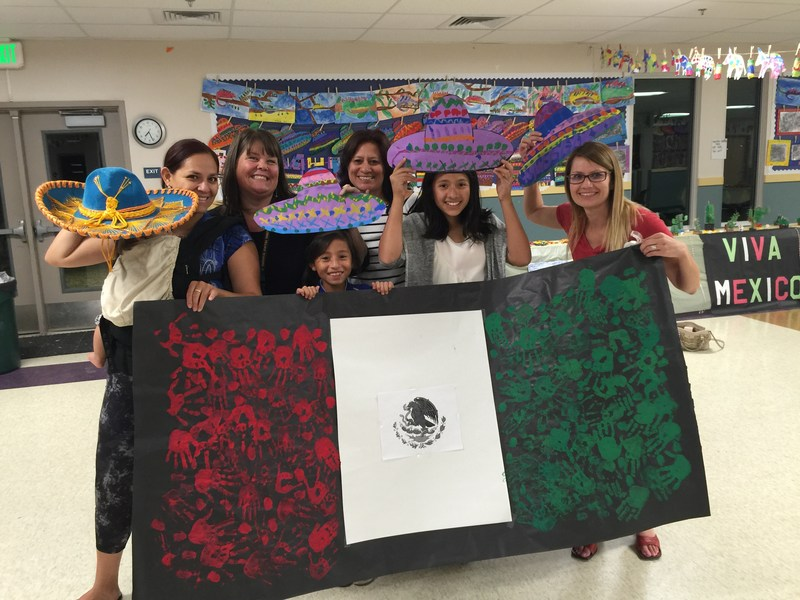 Teachers and students displaying a Mexican flag made with student handprints.