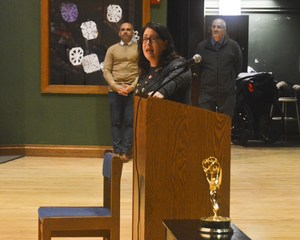 Ms. Dowd speaking with the Emmy in the foreground.
