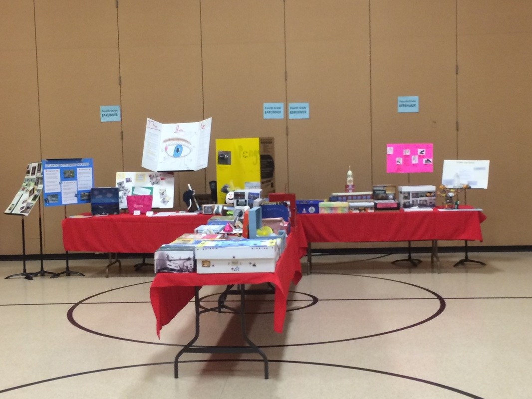 Tables with displays of science projects in a gymnasium