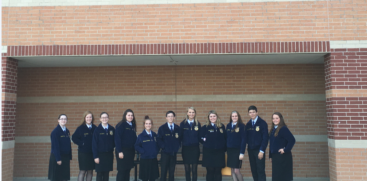Several FFA students posing in front of brick wall