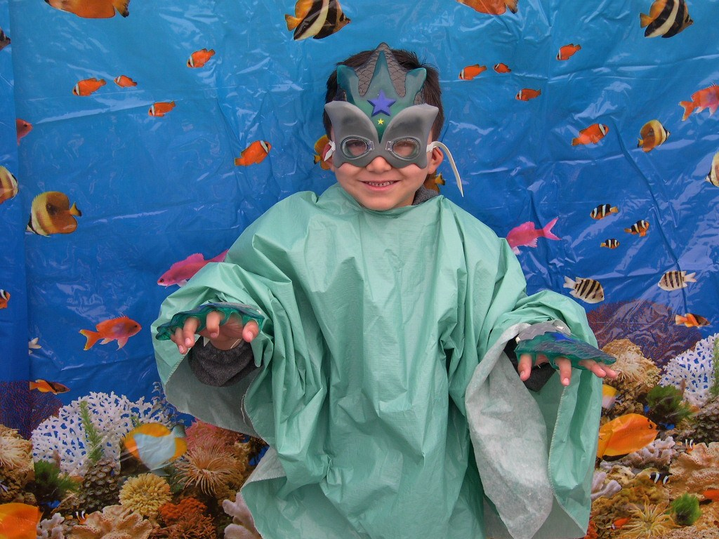 A boy dressed up as a fish in an underwater scene.