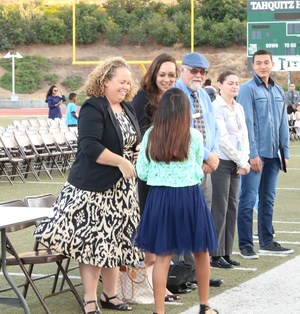 Board members shaking hands with students who were reclassified as English Proficient.