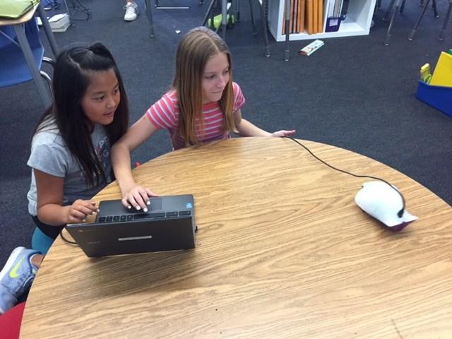 Two girls program a robot.