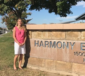 Tami Henry in front of a Harmony sign.