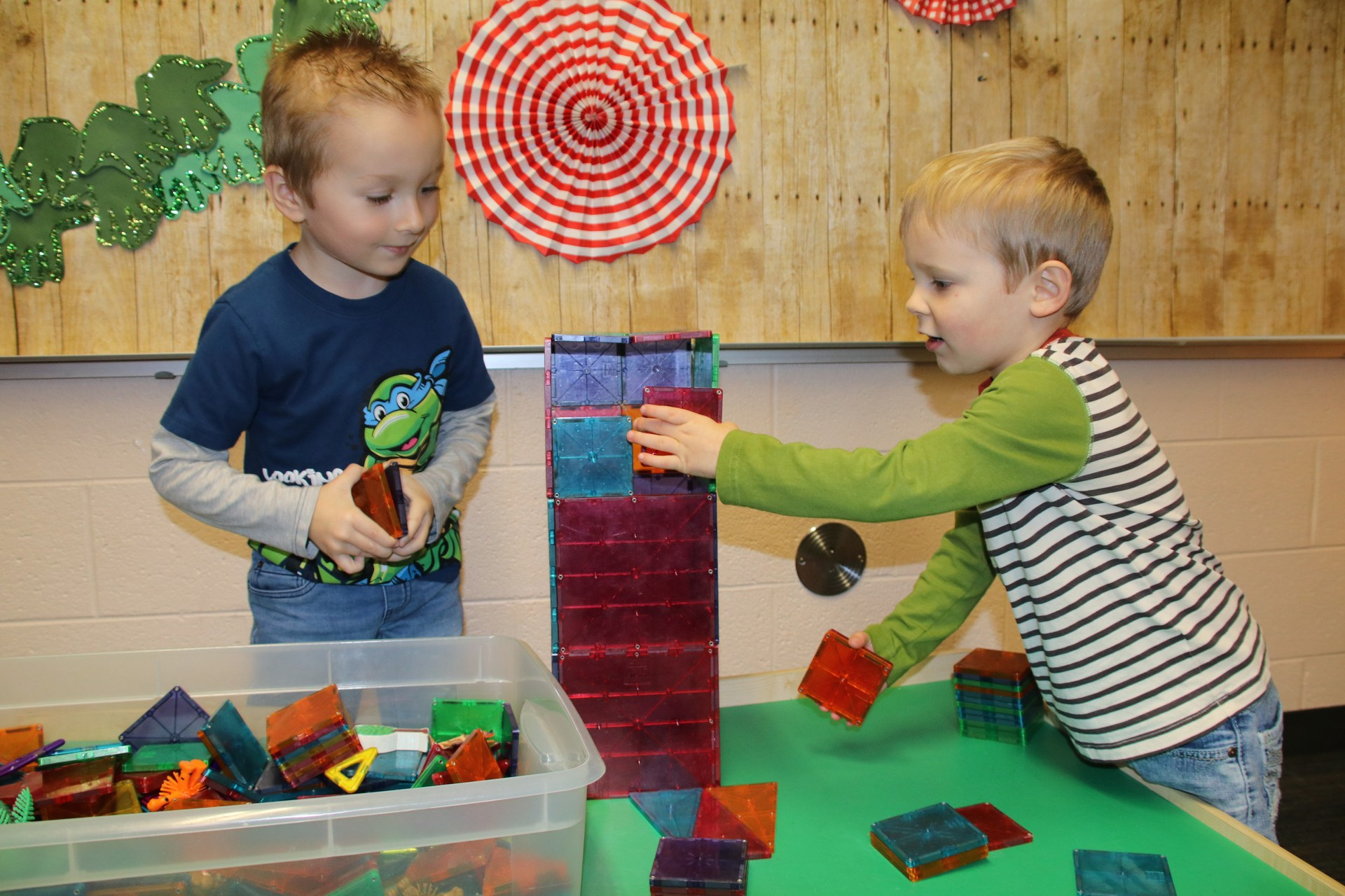 preschool boys stack magnetic pieces on table