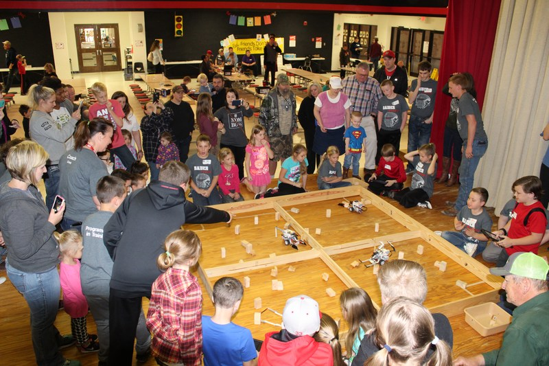 A group of students gathered around the center of the stage participating and watching fellow students in a robotics competition.