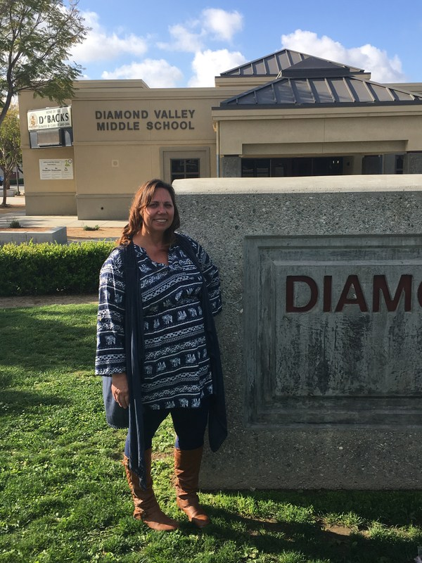 Laura Adams in front of the Diamond Valley Middle School sign