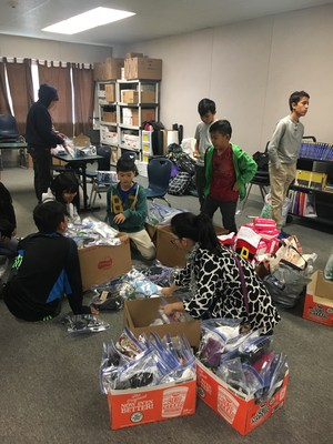 CCA students and families organize toiletry items for the homeless.