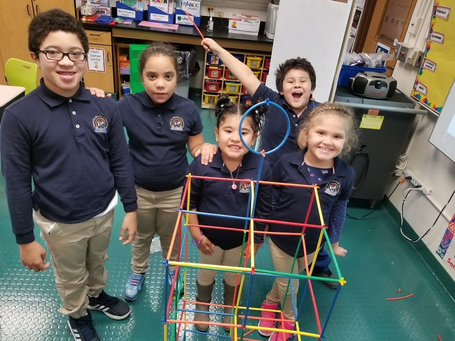children proudly displaying their group shape of multiple boxes linked