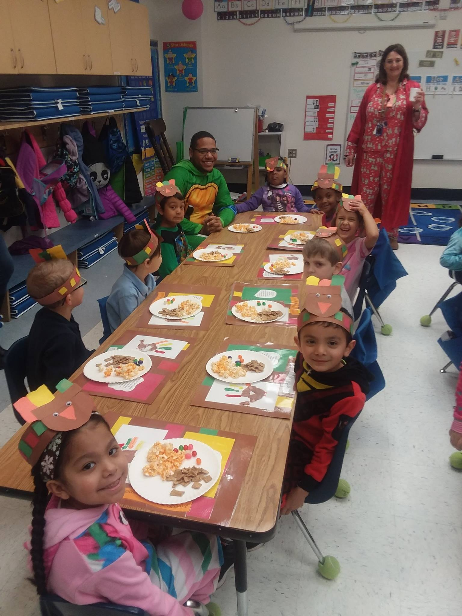 Mr. Smith enjoying a Charlie Brown thanksgiving meal with young 5 students.