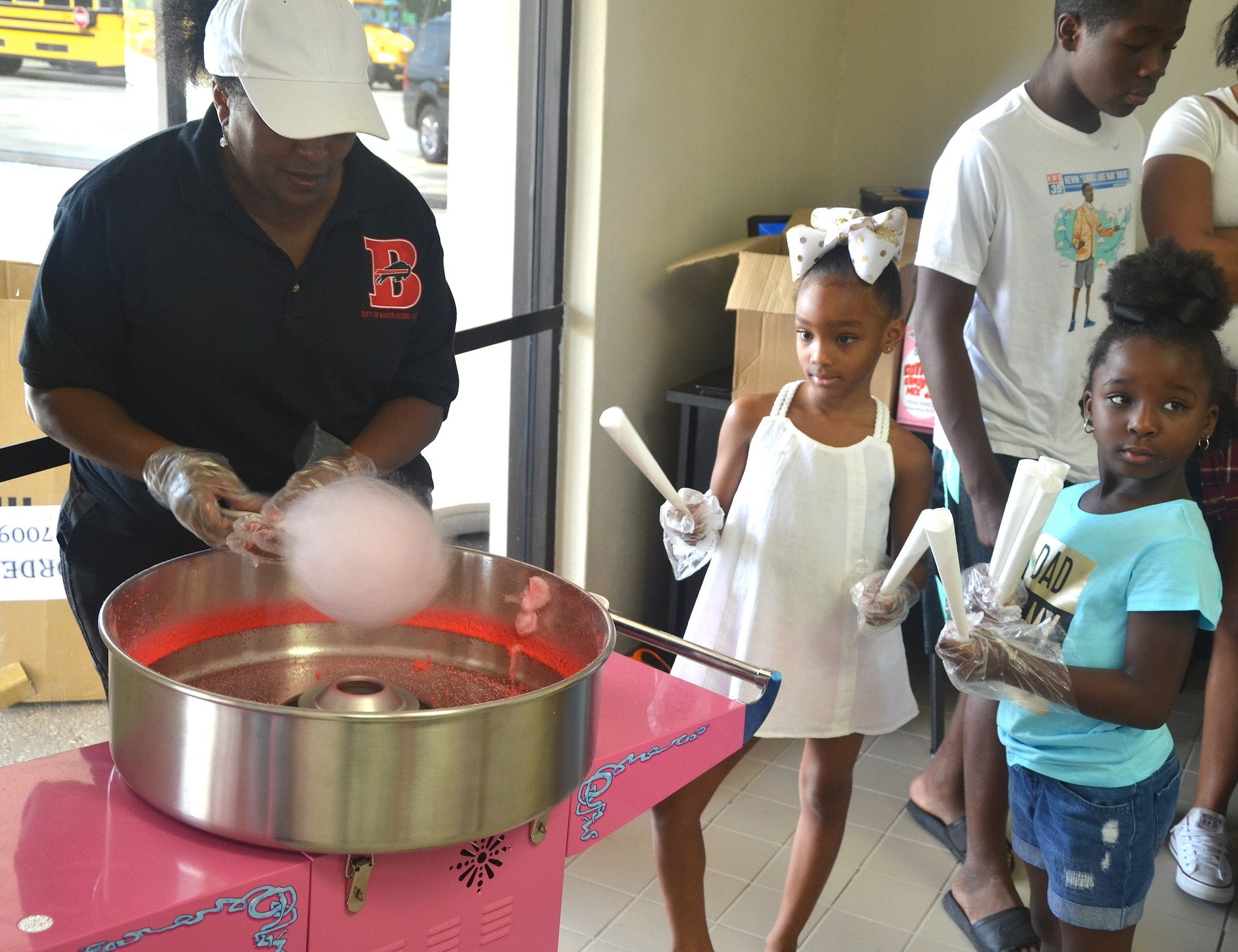 A photo of Miss Golden making and serving cotton candy to children at the 2017 Back To School Expo